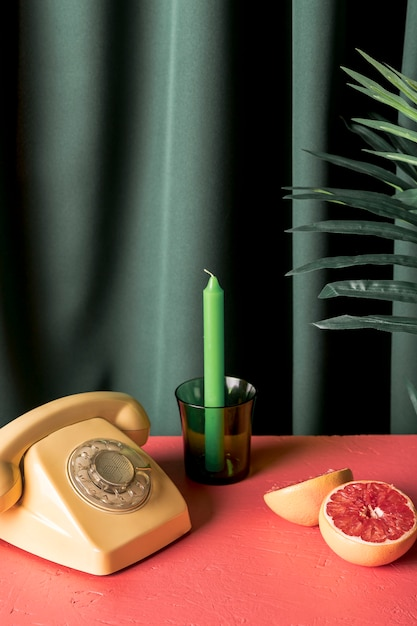 Téléphone rétro à côté de pamplemousse coupé en deux Photo gratuit