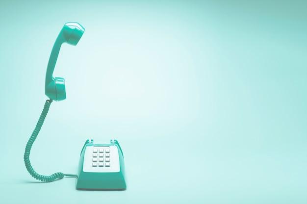 Téléphone vert rétro sur fond vert sarcelle Photo Premium