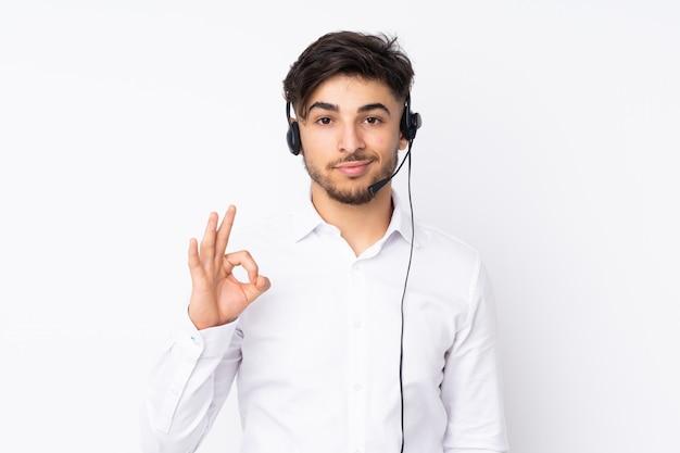 Télévendeur Homme Arabe Travaillant Avec Un Casque Isolé Sur Mur Blanc Montrant Un Signe Ok Avec Les Doigts Photo Premium