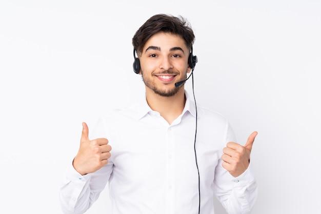 Télévendeur Homme Arabe Travaillant Avec Un Casque Sur Mur Blanc Donnant Un Coup De Pouce Geste Photo Premium