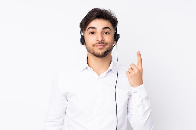 Télévendeur Homme Arabe Travaillant Avec Un Casque Sur Mur Blanc Pointant Avec L'index Une Excellente Idée Photo Premium