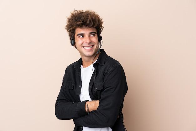 Télévendeur Homme Travaillant Avec Un Casque Sur Un Mur Isolé En Riant Photo Premium