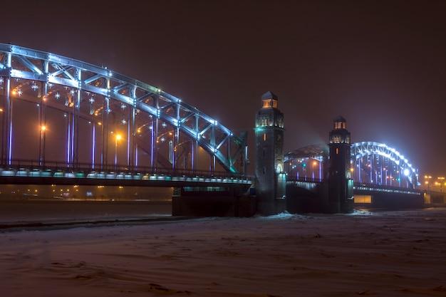 Tempête de neige en hiver dans la ville la nuit. pont bolchéokhtinsky à saint-pétersbourg, en russie Photo Premium
