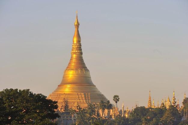 Temple de la pagode shwedagon avec village en bas à la lumière du matin à yangon, myanmar (birmanie) Photo Premium