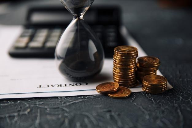 Le Temps Est Un Concept D'argent. Signature D'un Contrat. Pièces Et Sablier à Côté De La Calculatrice Sur Un Contrat Photo Premium