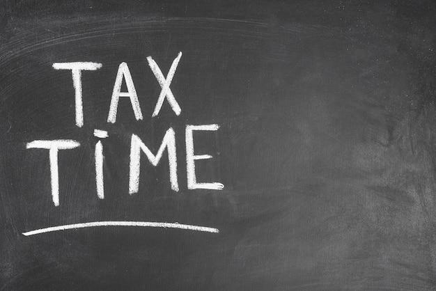 Temps d'impôt écrit le texte sur le panneau noir Photo gratuit