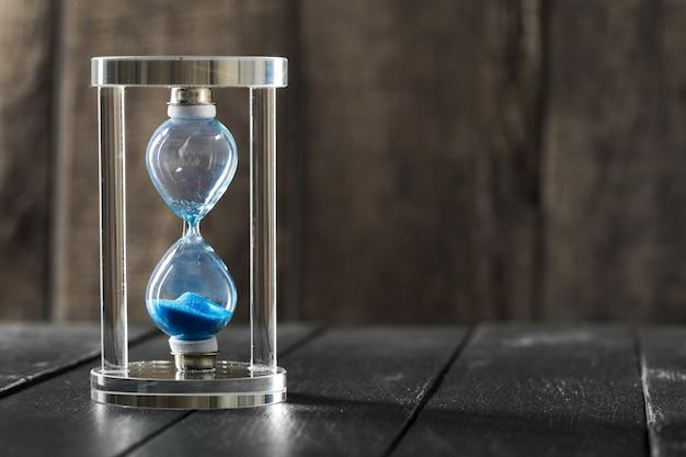 Le temps passe. sablier bleu se bouchent Photo Premium