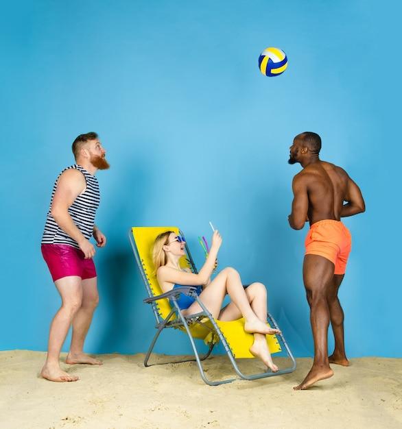 Temps Pour L'activité. Des Amis Heureux Prennent Selfie, Jouant Au Volleyball Sur Fond Bleu De Studio. Concept D'émotions Humaines, Expression Faciale, Vacances D'été Ou Week-end. Chill, été, Mer, Océan. Photo gratuit