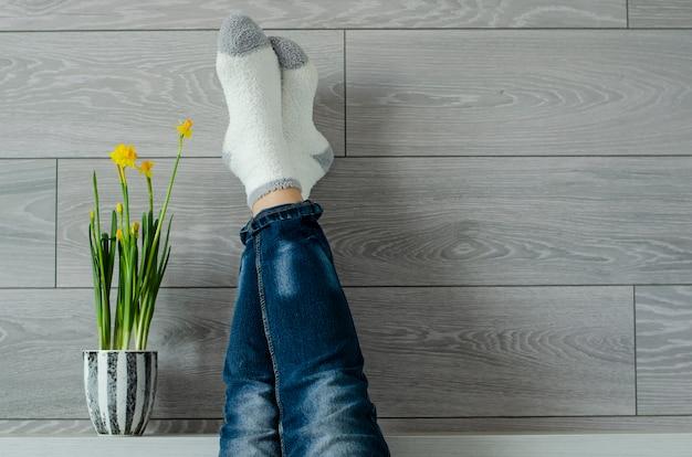Temps pour se détendre. jambes féminines vers le haut sur le mur et le pot de fleurs avec narcisse. Photo Premium