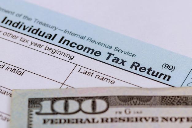 Temps des taxes gros plan d'une déclaration de revenus us 1040 avec 100 factures Photo Premium