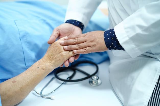 Tenant la main asiatique patiente âgée ou âgée vieille dame avec amour, soin, encourager Photo Premium