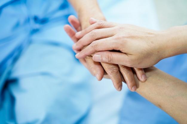 Tenant la main asiatique vieille dame âgée patiente avec amour, soin, encouragement et empathie. Photo Premium