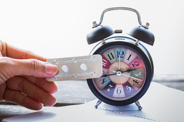 Tenant Un Médicament De Contrôle Des Naissances D'urgence Avec Une Horloge Alam Vintage. Photo Premium