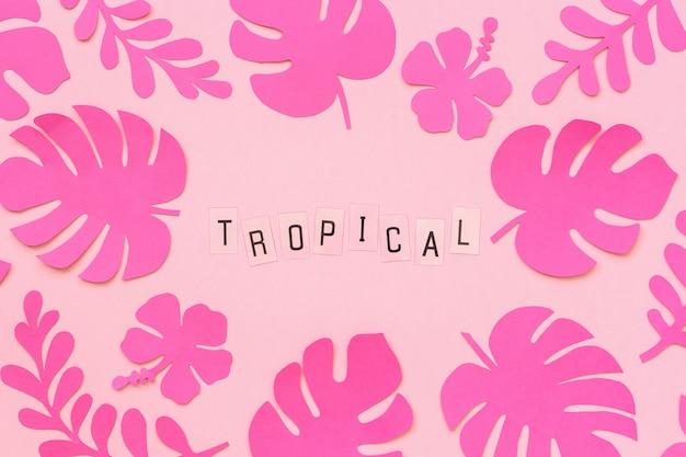 Tendance des feuilles tropicales roses de papier et texte inscription tropicale sur fond rose. Photo Premium