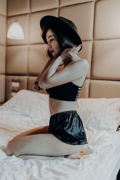 Tendre Belle Femme En Sous-vêtements De Mode Et Chapeau Assis Sur Le Lit Le Matin Photo gratuit