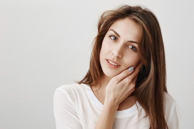 Tendre Belle Femme Touchant La Peau Douce Et Regardant Photo gratuit