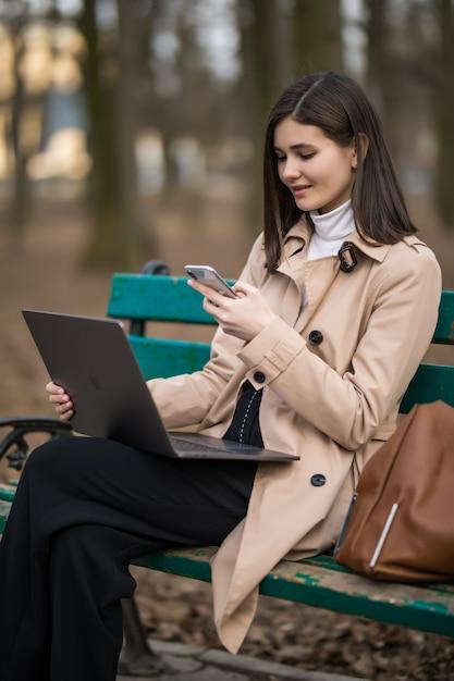 Tendre Brunette Mannequin Fille Travaille Sur Ordinateur Portable Et Téléphone à L'extérieur Dans Le Parc Photo gratuit