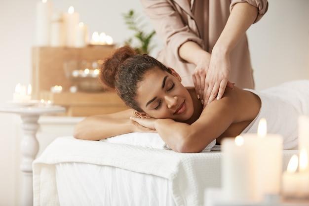 Tendre Femme Africaine Souriante Bénéficiant D'un Massage Avec Les Yeux Fermés Dans La Station Thermale. Photo gratuit