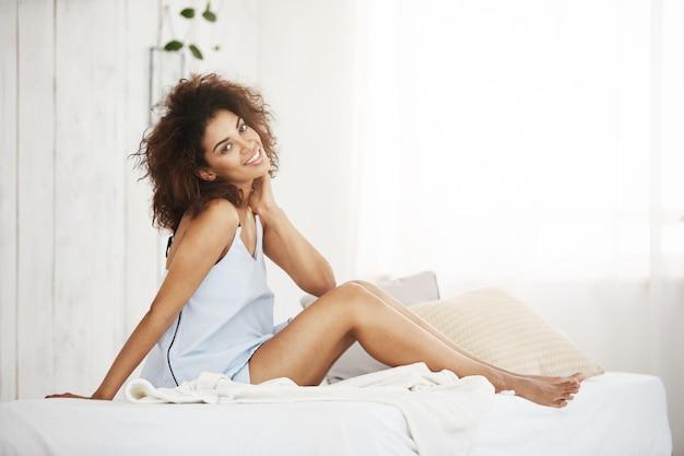 Tendre Femme Africaine En Vêtements De Nuit Assis Sur Le Lit à La Maison En Souriant. Photo gratuit