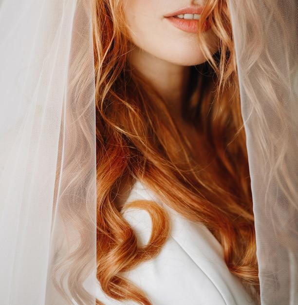 Tendre les lèvres et la peau de la charmante mariée aux cheveux bouclés roux Photo gratuit