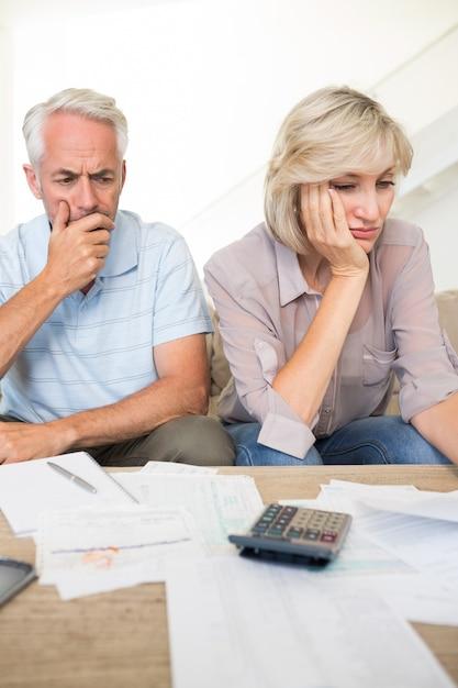 Tendu homme mûr et femme avec factures et calculatrice assis sur le canapé à la maison Photo Premium