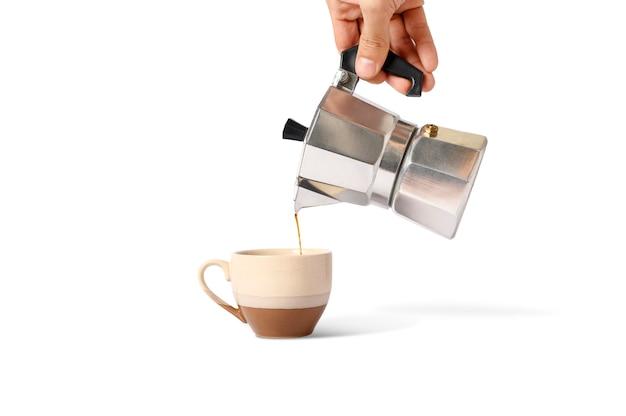 Tenir Le Pot Moka Avec Verser Du Café Sur Une Tasse Isolée. Photo Premium