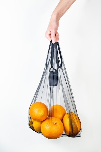 Tenir Un Sac De Ficelle Réutilisable Plein D'oranges. Photo Premium