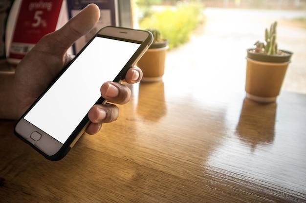 Tenir le téléphone portable et jouer à l'application dans le café Photo Premium