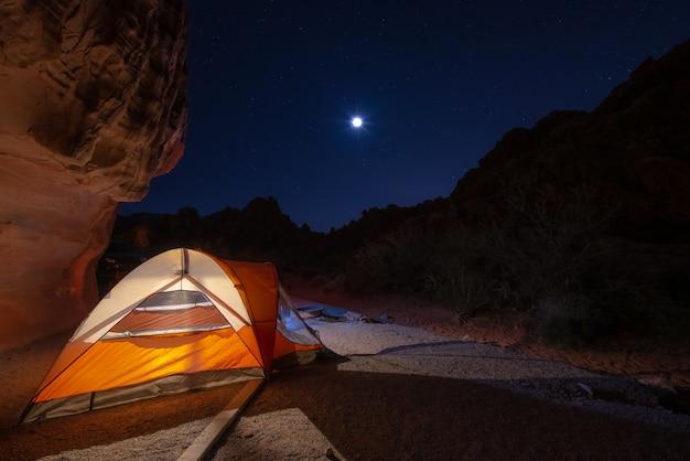 Tente orange campant la nuit avec la lune et les étoiles dans le ciel Photo Premium