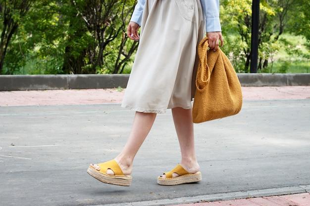 Tenue de mode d'été. fille en robe, chaussures jaunes et sac en maille tendance, vue de côté Photo Premium