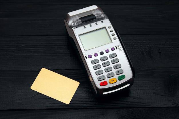 Terminal bancaire et carte de paiement sur fond noir Photo Premium