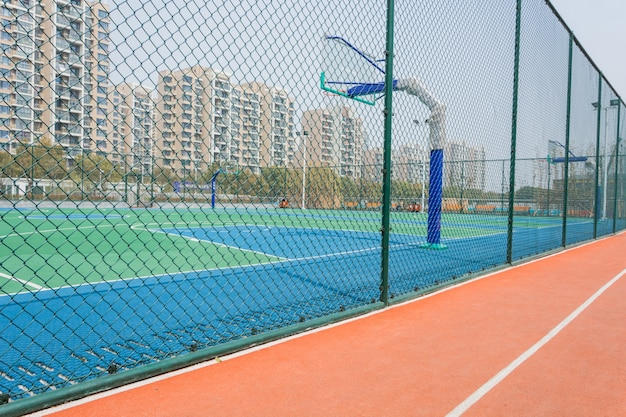 Terrain de basket avec une clôture de fil autour Photo gratuit