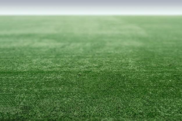 Terrain de sport vert avec gazon artificiel, perspective du terrain de football. Photo Premium
