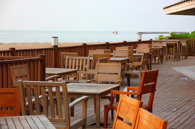 Terrasse en bois avec table et bureau en bois sur la plage au point de vue mer Photo Premium