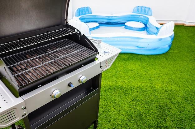 Terrasse Avec Gazon Artificiel, Barbecue Et Piscine En Caoutchouc Pour Rester à La Maison En été. Photo Premium
