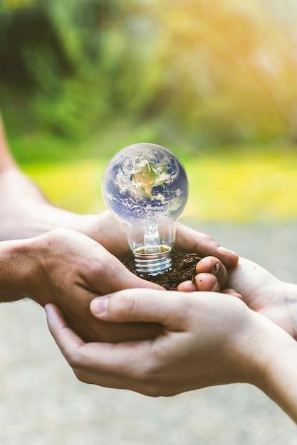 Terre concept à l'intérieur de l'ampoule dans les mains Photo gratuit