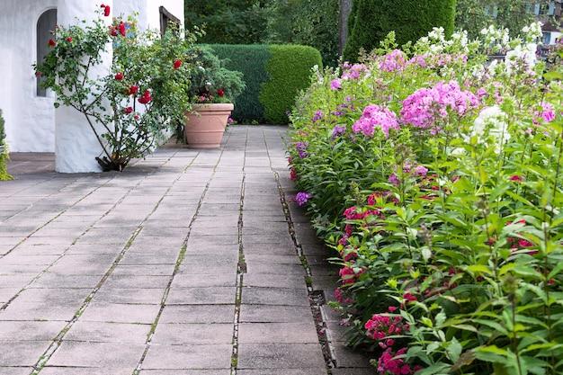 Territoire de la maison décoré de fleurs de phlox, de roses et de haies. Photo Premium