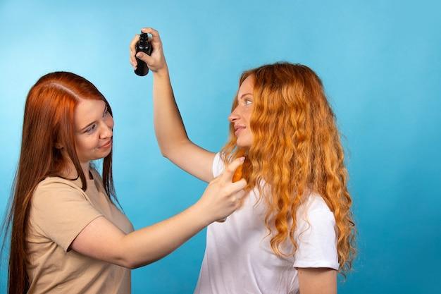 Test D'arôme. Les Filles Aux Cheveux Longs Se Vaporisent Du Parfum Les Unes Sur Les Autres. Photo Sur Mur Bleu. Photo Premium