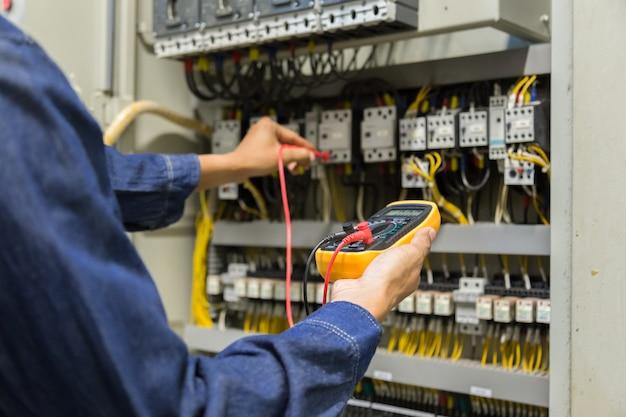 Testeur de travaux d'ingénieur électricien mesurant la tension et le courant de la ligne électrique de puissance dans le contrôle d'armoire électrique. Photo Premium