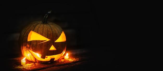 Tête de citrouille d'halloween avec des bougies allumées Photo Premium