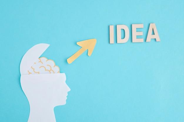 Une tête humaine en papier ouvert avec une flèche jaune pointant vers une idée de mot sur fond bleu Photo gratuit
