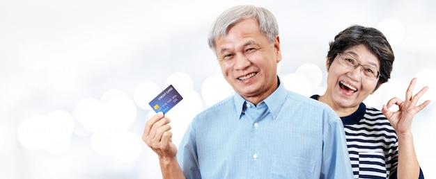 En-tête de joyeux couple de personnes âgées gaies, retraités ou parents plus âgés souriant et montrant une carte de crédit Photo Premium