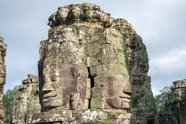 Tête de pierre sur les tours du temple bayon à angkor thom, cambodge Photo Premium