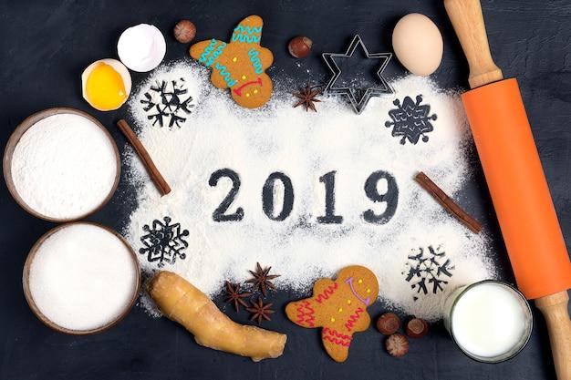 Texte de 2019 fait avec de la farine avec des décorations sur fond noir au pain d'épice noël Photo Premium