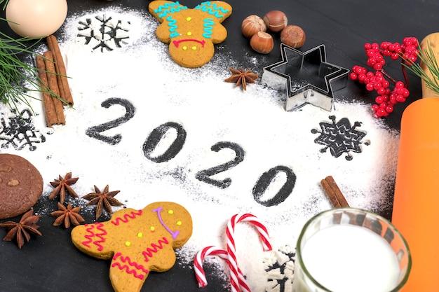 Texte 2020 fait avec de la farine avec des décorations sur fond noir. lay plat. Photo Premium
