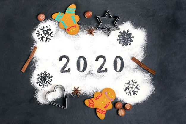 Texte 2020 fait avec de la farine avec des décorations sur fond noir. Photo Premium
