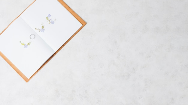 Texte d'amour fait avec bague de mariage sur un livre ouvert sur fond de béton Photo gratuit