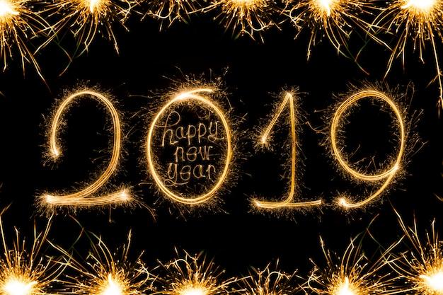Texte de bonne année 2018 écrit avec des feux d'artifice d'étincelle isolé sur fond noir Photo Premium