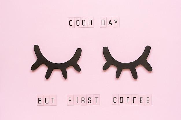 Texte bonne journée, mais premier café et cils noirs en bois décoratifs, yeux fermés, sur papier rose pastel Photo Premium
