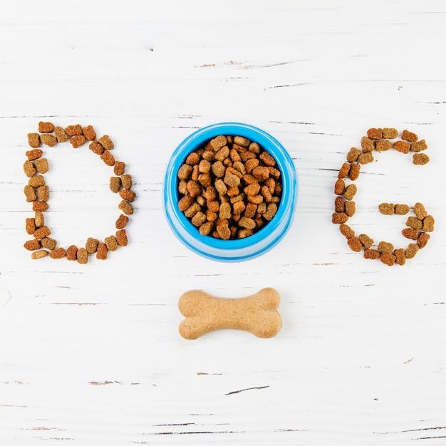 Texte chien avec os sur une surface en bois blanche Photo gratuit